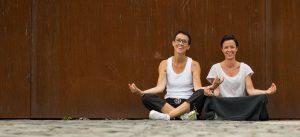 Sandra und Heidi sitzen meditierend im Schneidersitz auf dem Boden